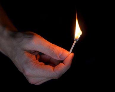 adult man hand holding matchstick